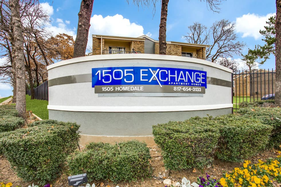 Front sign of 1505 Exchange with manicured hedges and palm trees.
