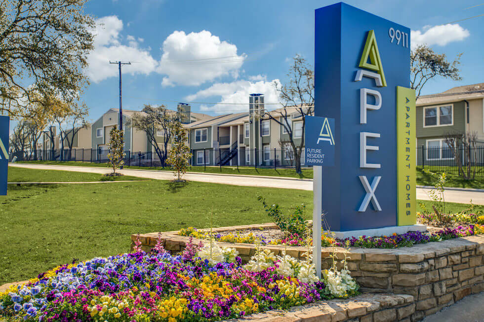 Vertical blue sign for The Apex in a stone bordered flowerbed.