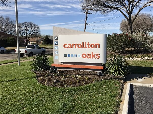Carrollton Oaks sign in small flowerbed.