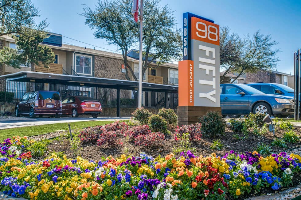 Orange and blue sign for 98Fifty on top of stone pillar surrounded by matching flowers.